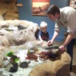 Man showing a young child the tidepool
