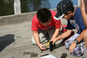 Two children collecting data by the water