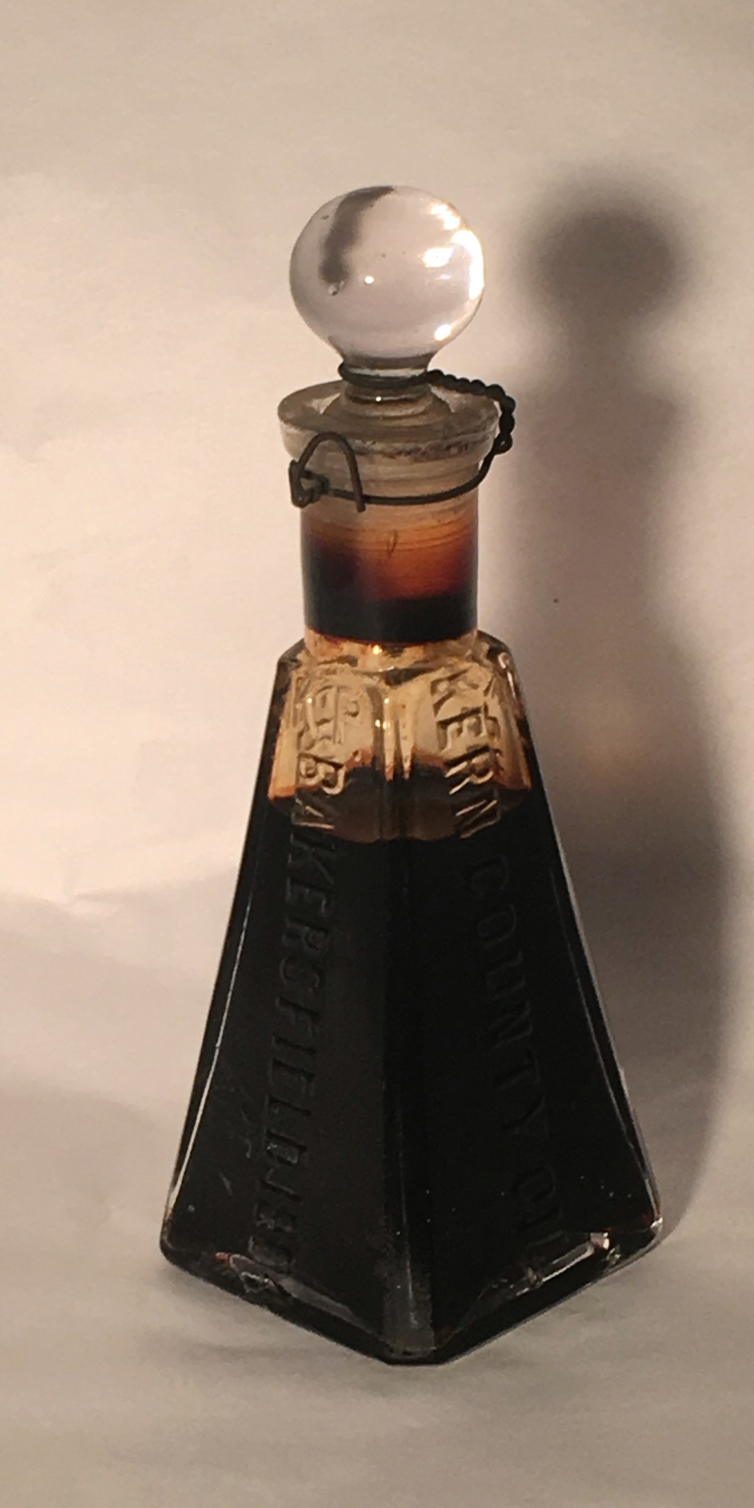 A four sided glass jar with a stopper filled with black oil.