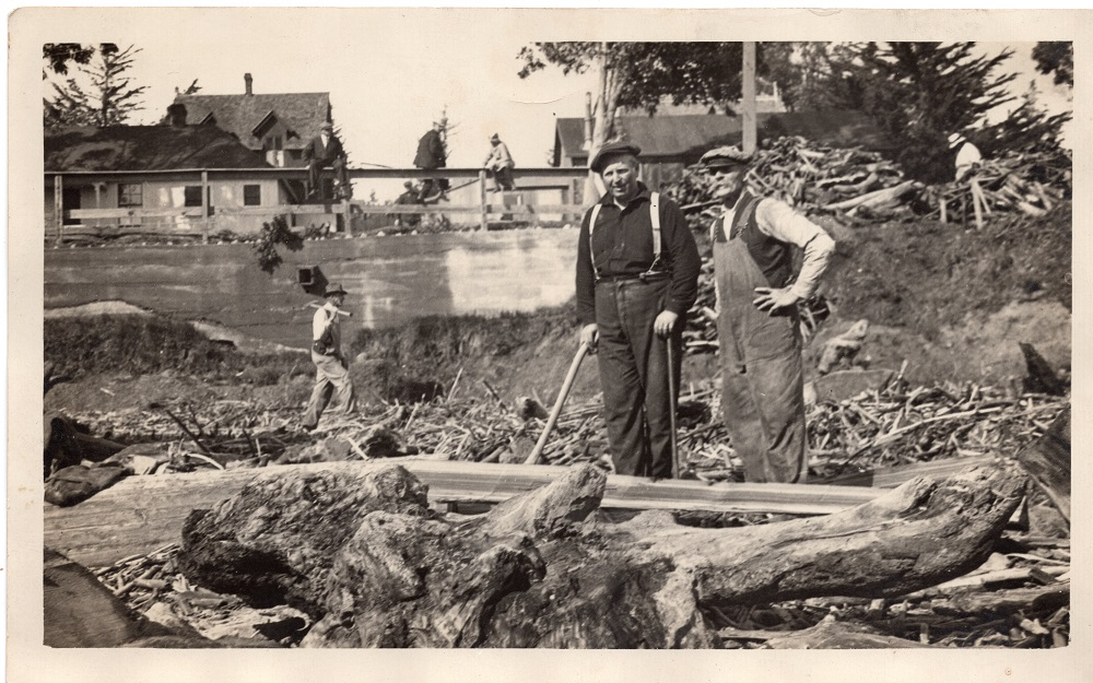 Louis and Conrad Scholl standing among driftwood on Seabright Beach, 1930s.