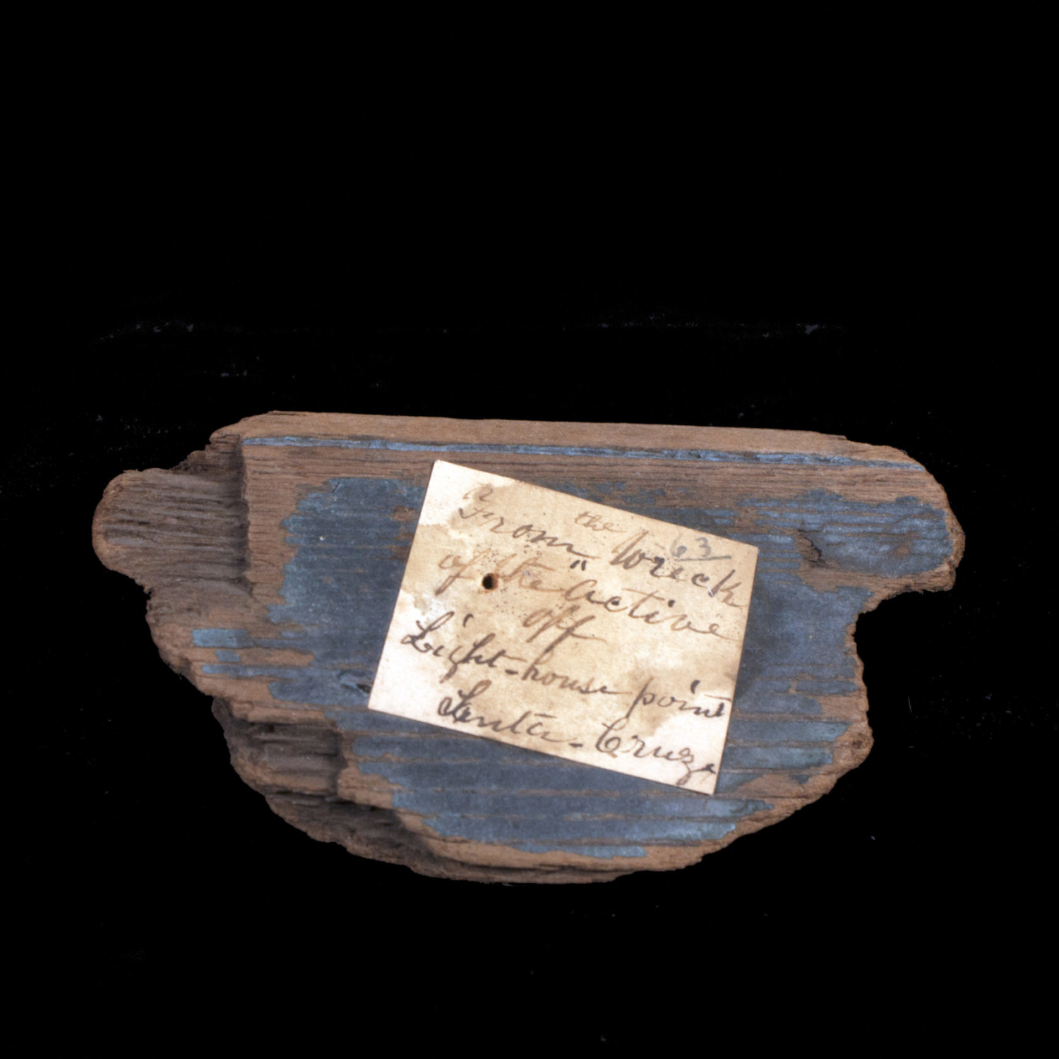 A piece of wood from a ship with a handwritten identification note on it.