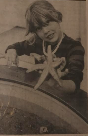 A black and white image of a girl holding up a sea star from a 1977 Sentinel article.