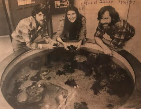 Museum staff in 1977 stand around the then new touch pool exhibit.