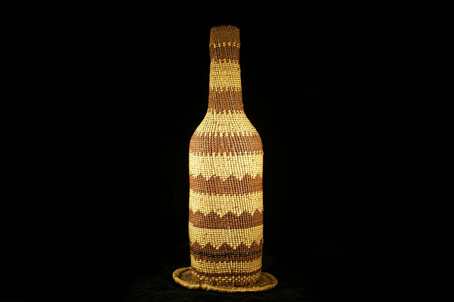 Glass bottle wrapped in basketry, made by the Klamath River Tribes