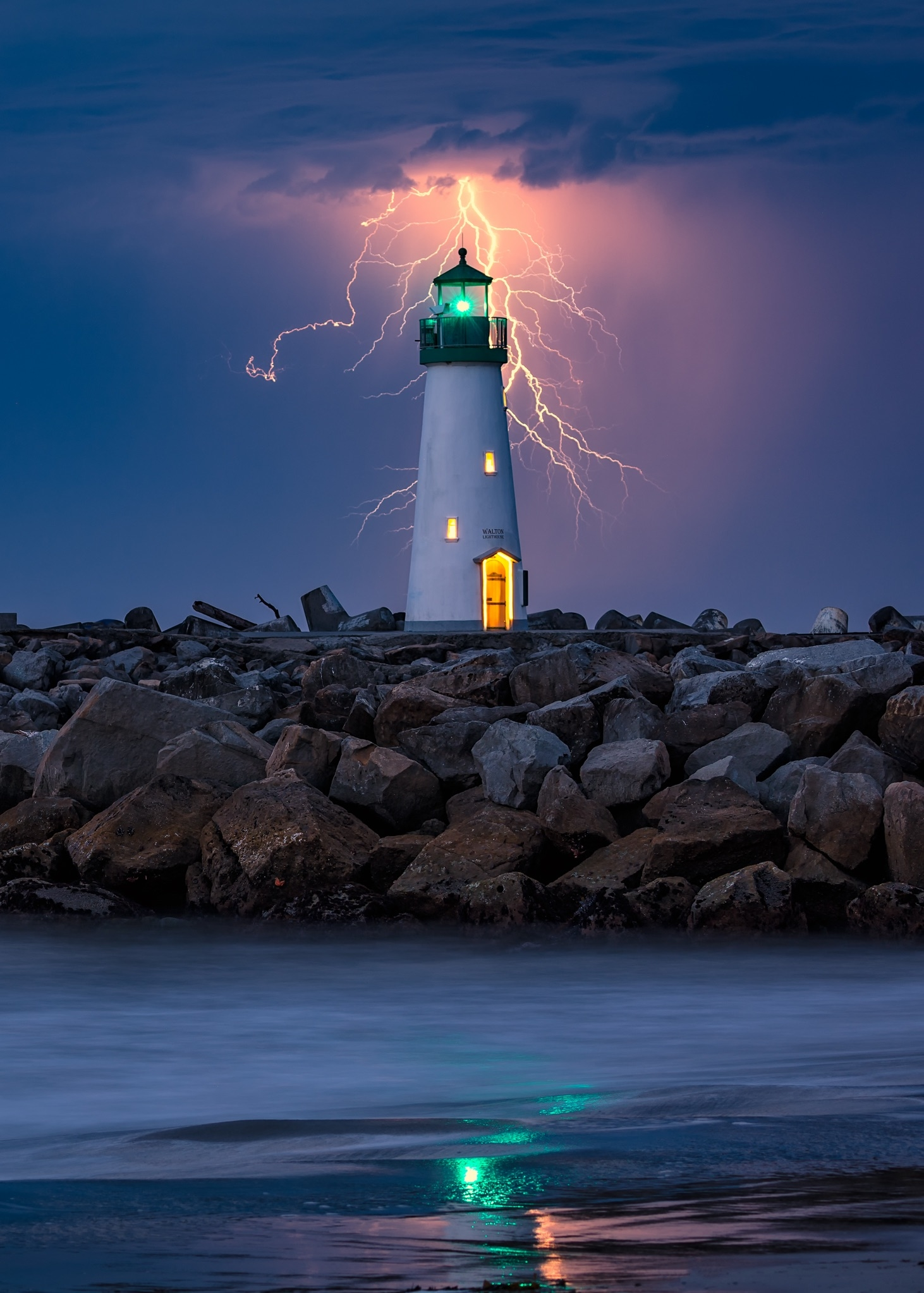 Lightning flashes straight down leading towards the shining green light of the Walton Lighthouse at the Santa Cruz Harbor.