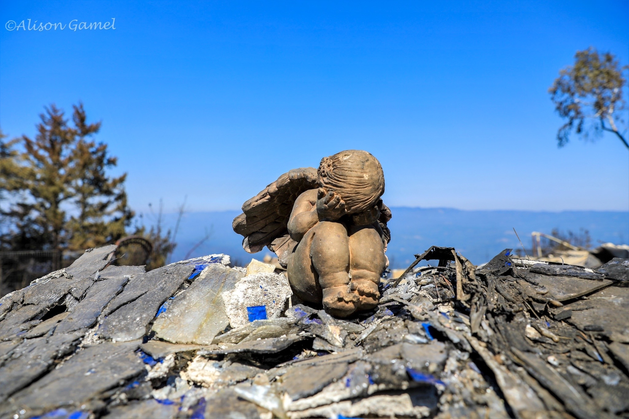 A stone sculpture of an angel with its head in its lan sits atop a pile of rubble with a clear blue sky behind it.