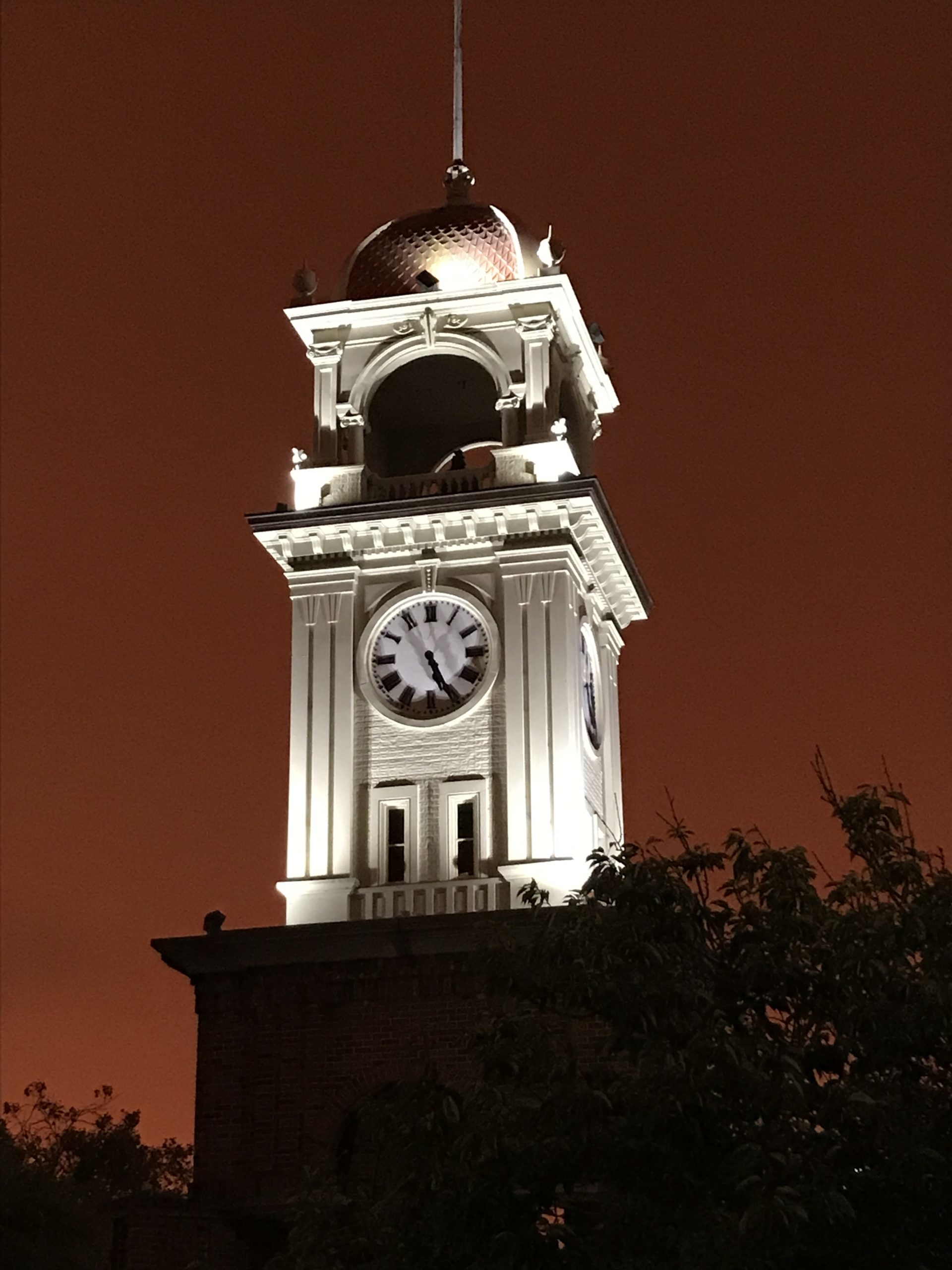 A light-up white clock tower with a dark orange sky background.