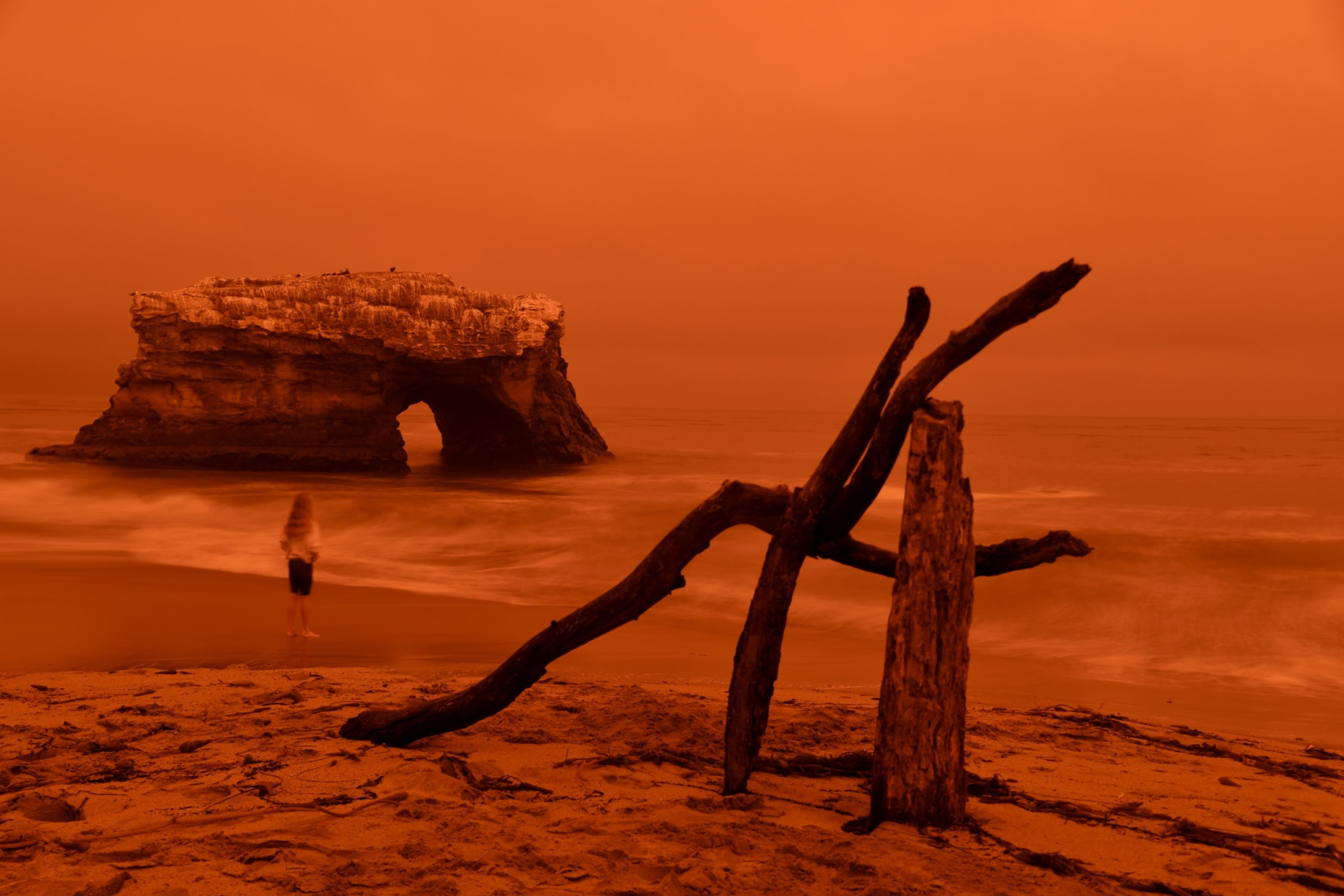 A small sculpture of driftwood stuck in the sand is in the forefront, with the Natural Bridges arch in the background and person approaching the water, all cloaked in a bright red hue.
