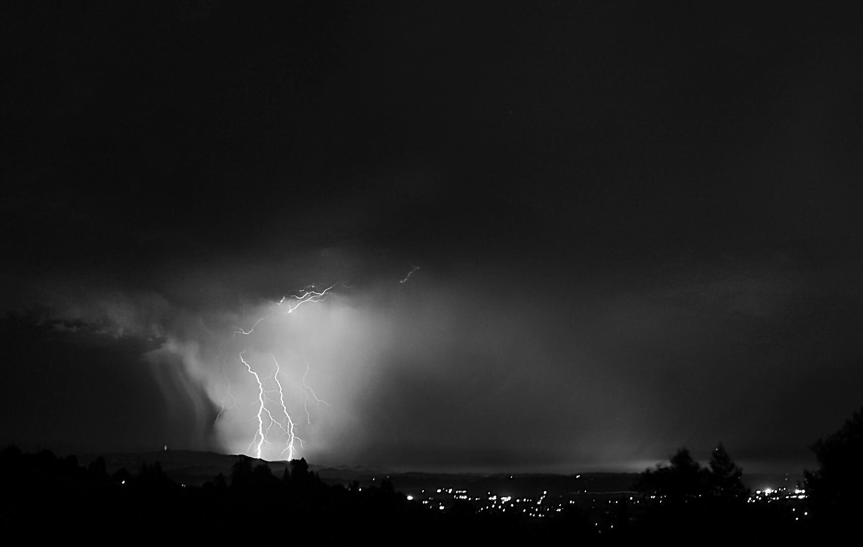 A black and white image of lightening (left) over some city lights.