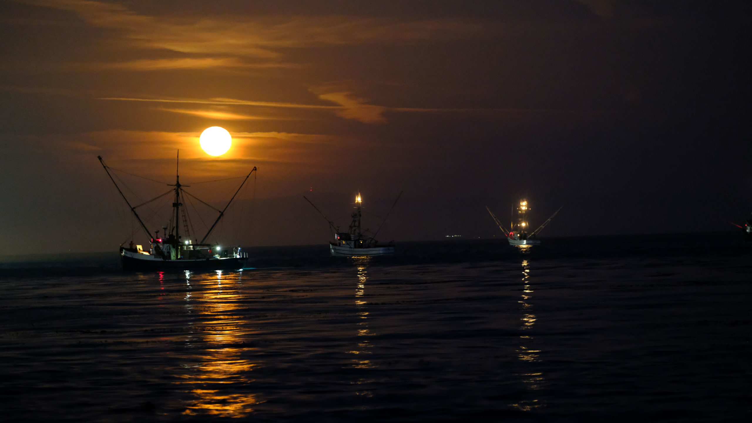 Three fishing boats in the ocean with a bright full moon behind them.