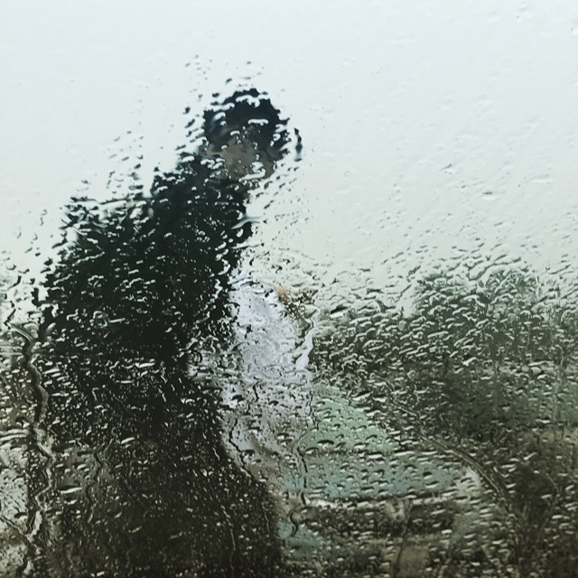The silhouette of a figure walking past cars is obscured with rain on a glass window.