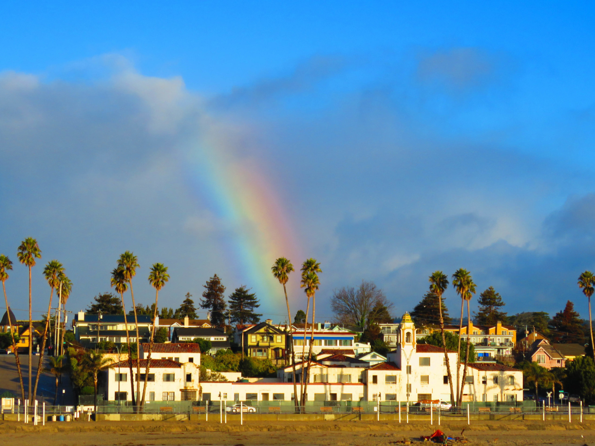 A skyline of palm trees and a white complex with a rainbow leading down towards the tower.