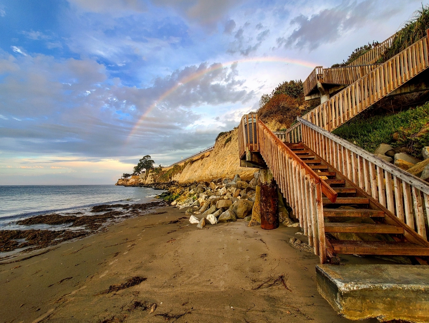 Stairs lead off of a beach with a rainbow in the sky behind.