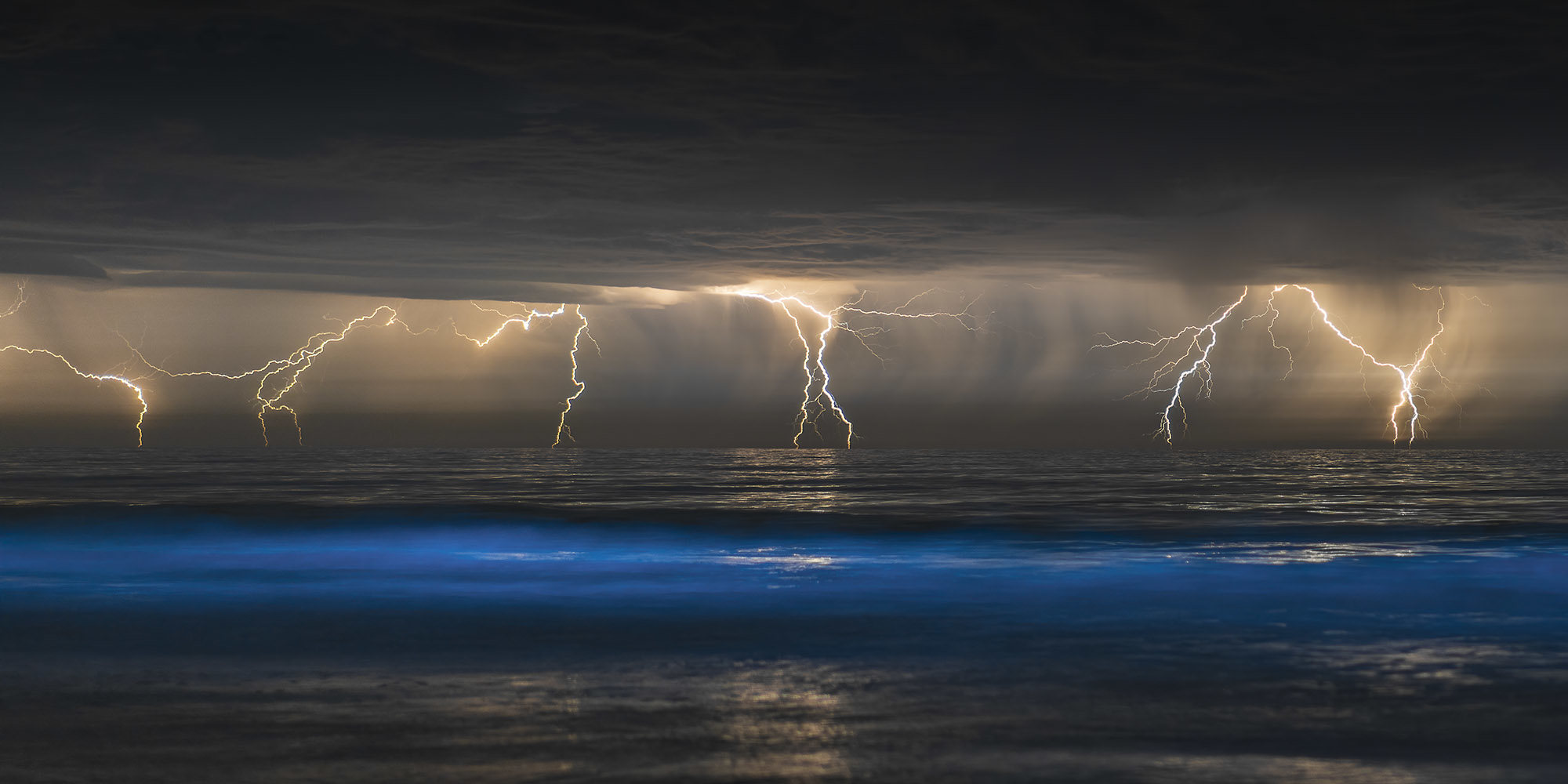 A series of lightening bolts descends grey clouds towards the ocean, with a cresting wave of glowing blue in the foreground.