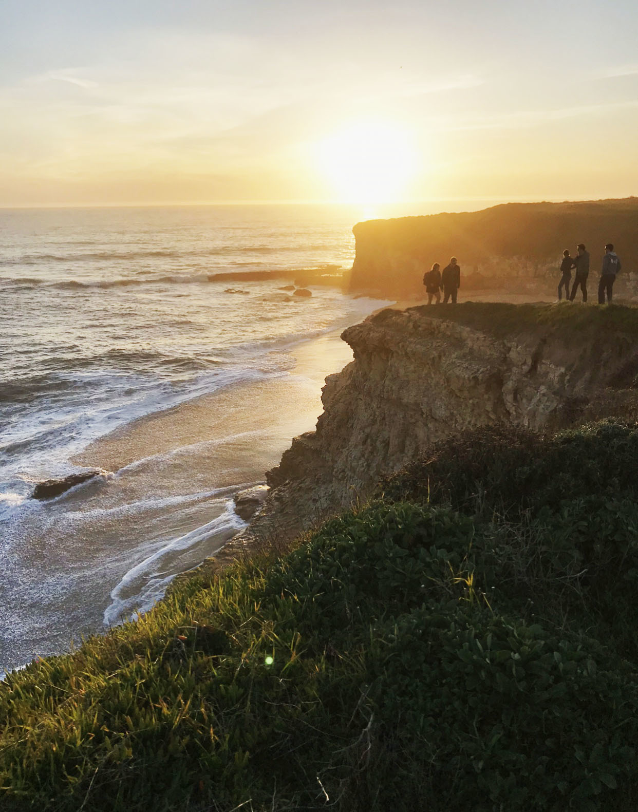 A series of tall cliffs speckled with people along the coast with the sunsetting in the distance