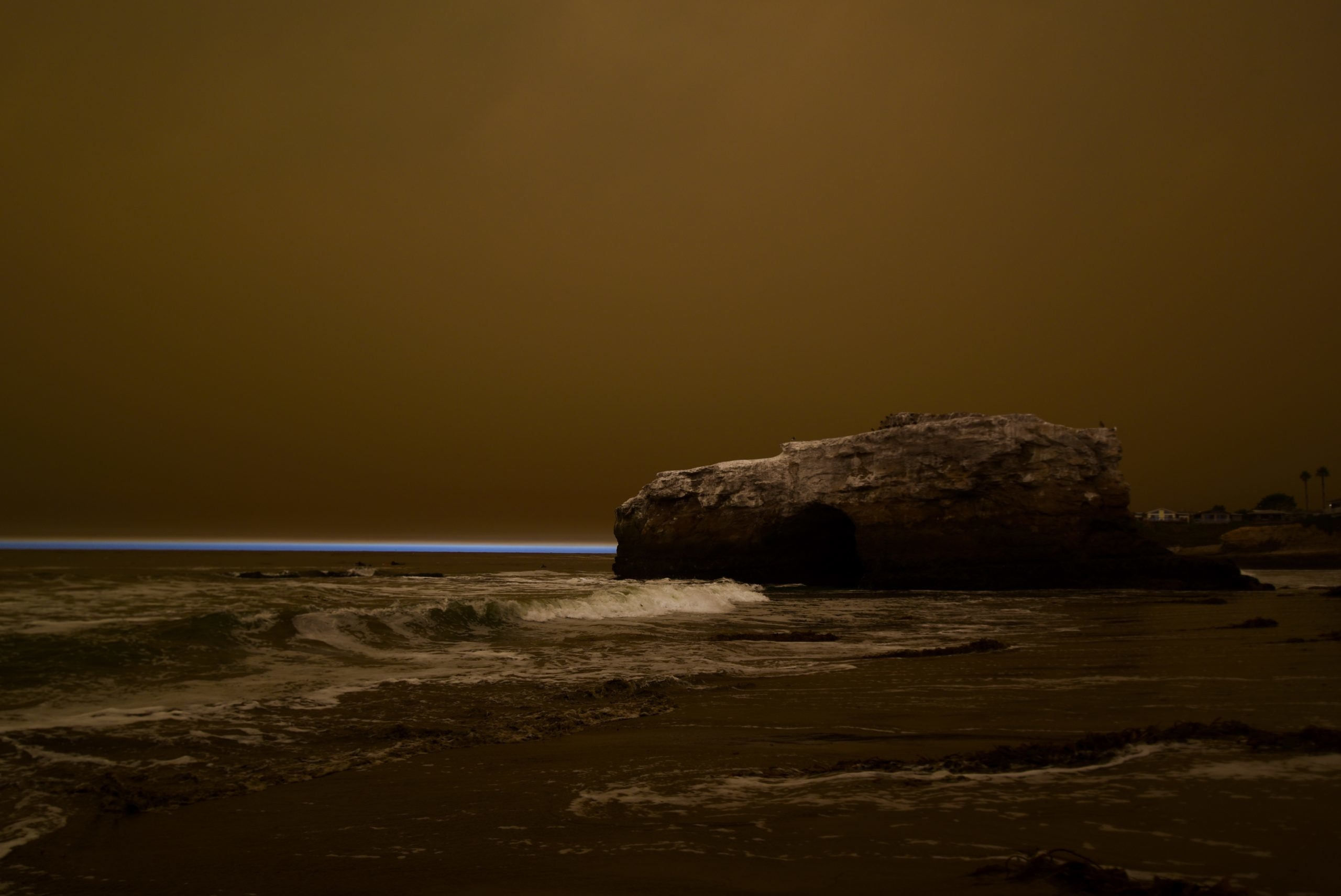 A rock pillar along the beach under a brown sky with a thin sliver of blue along the horizon.