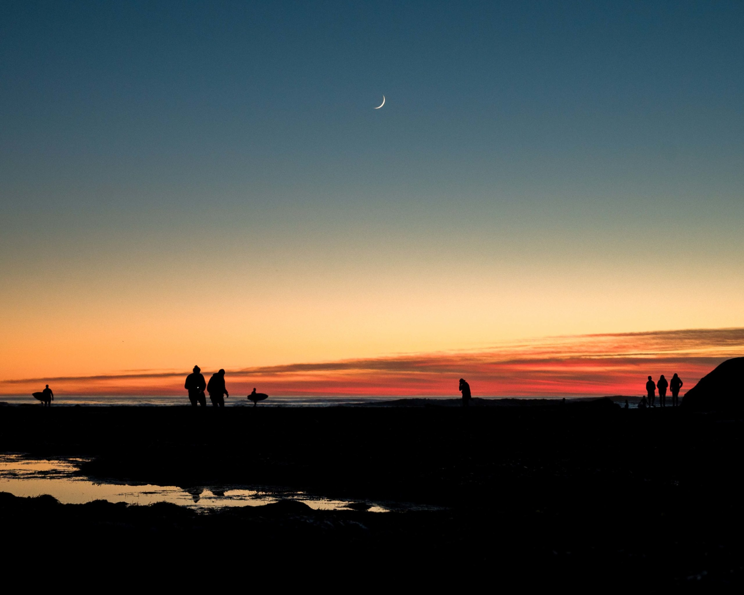 Silhouettes of people in the distance exploring the intertidal zone at sunset.
