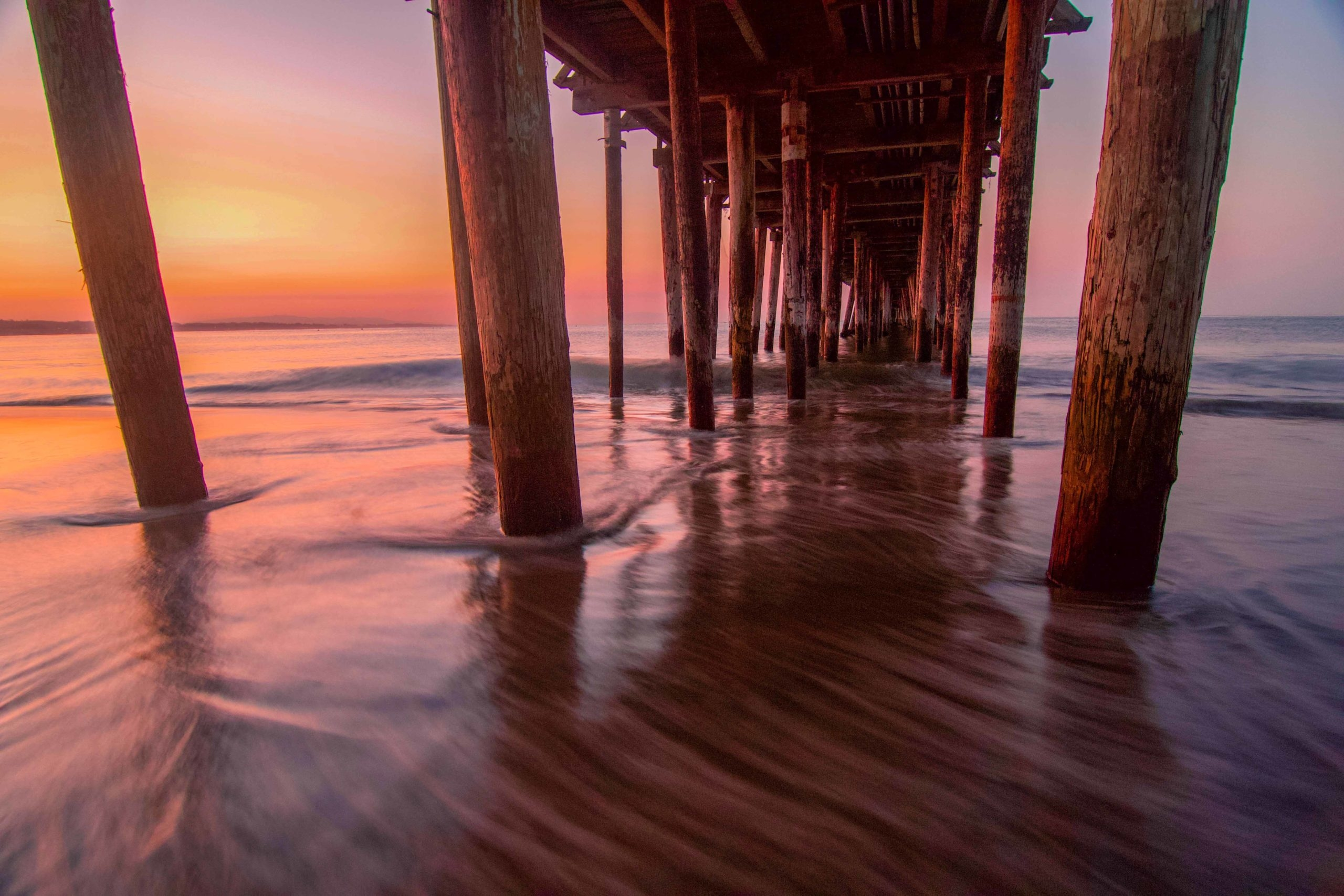 The pillars of the pier extend out into the ocean on both sides, with soft waves under a purple and orange sky.
