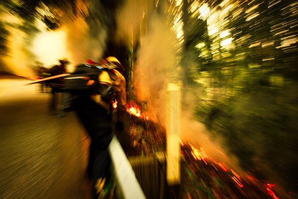 A blurred image centers on a fire fighter approaching a burning hillside.