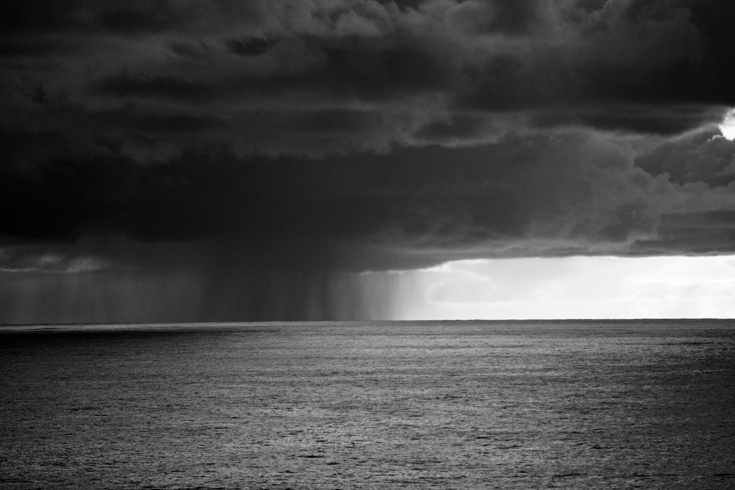 A black and white image of a dark grey cloud hovering over the ocean, rain forming to the left.