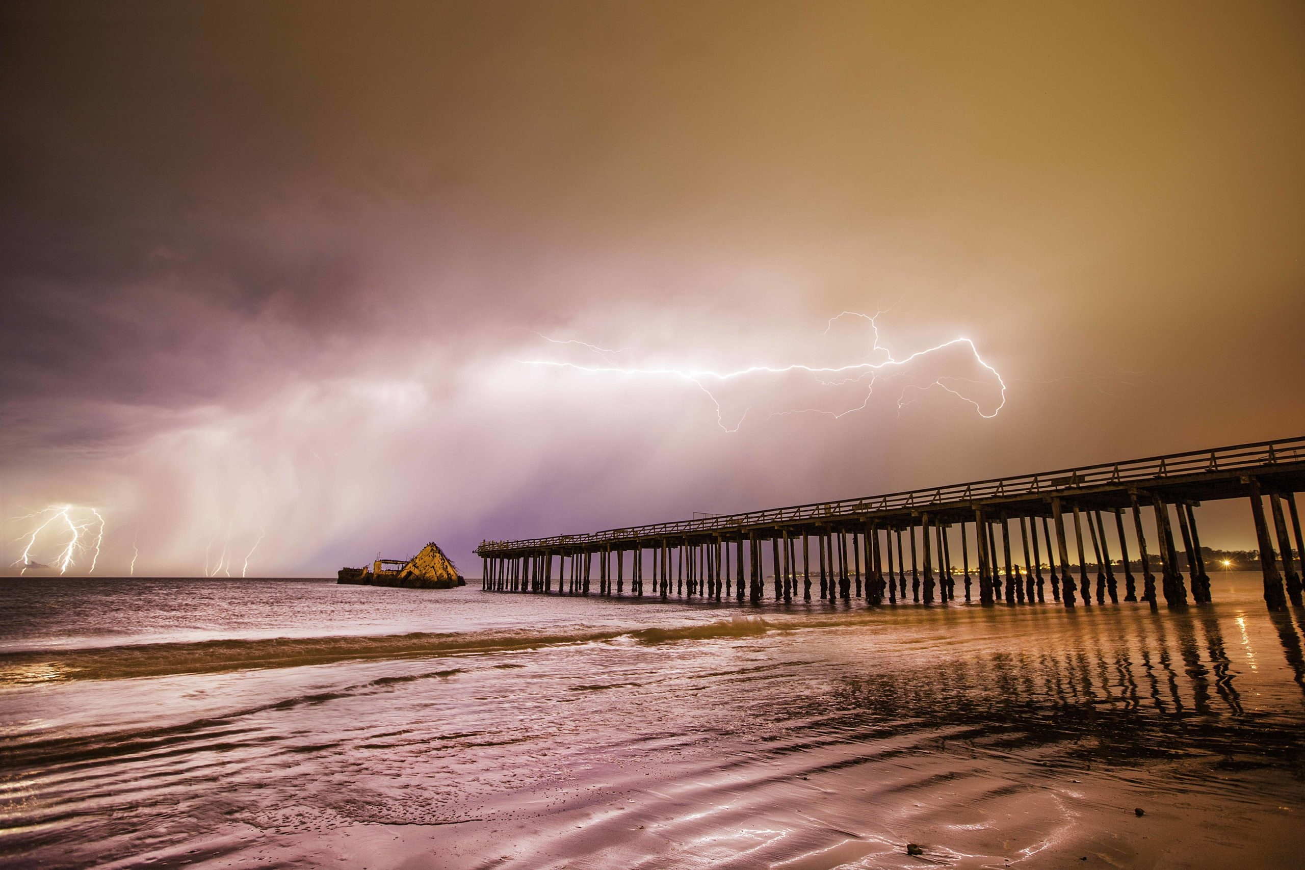 A bright purple and pink view of the cement ship at the end of a pier with a bolt of lightening creeping across the sky above.