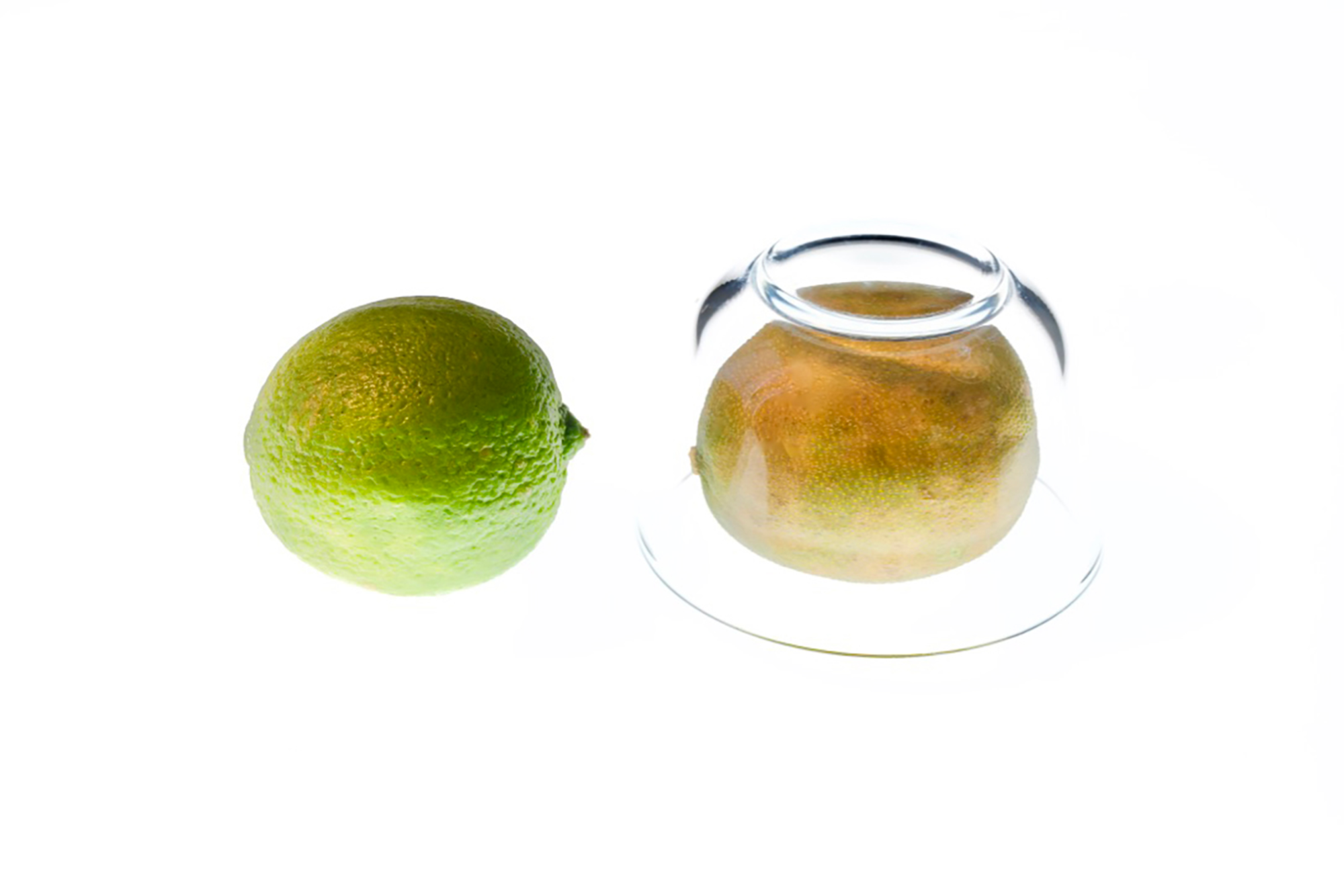 Two limes lie next to each other, one covered with a glass dish and browning.