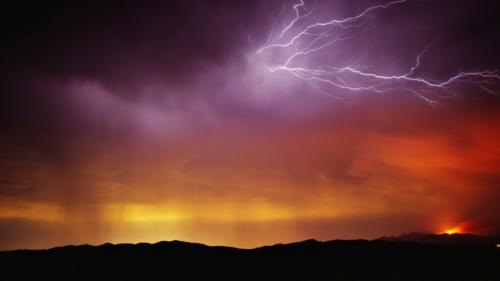 Lightning flashes through purple clouds over the horizon glowing orange.